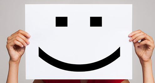 graphic for IT support with a person holding a smiley poster in front of their face
